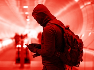 A man in a subway tunnel wearing gloves and a hoodie, looking at a mobile phone. Photo by Lorado / Getty Images
