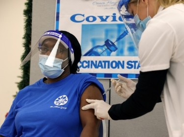 Denise Gregory, a staff member at Crown Heights Center for Nursing and Rehabilitation, a nursing home facility, receives the COVID-19 vaccine from Walgreens Pharmacist Annette Marshall, in Brooklyn, New York, December 22, 2020, photo by Yuki Iwamura/Reuters