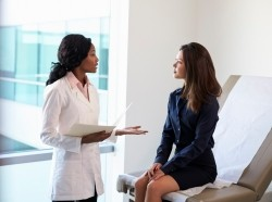 A doctor meeting with a female patient in an exam room