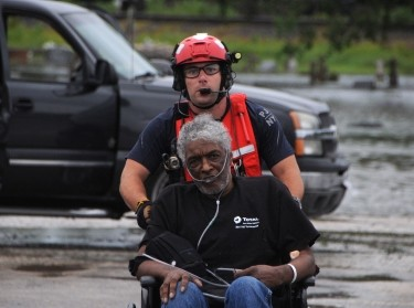 Senior Airman John J. Kosequat, a pararescueman with the 103rd Rescue Squadron of the 106th Rescue Wing assigned to the New York Air National Guard, pushes an elderly man toward the HH-60 Pave Hawk helicopter in Houston area, August 30, 2017. (U.S. Air National Guard photo by Daniel H. Farrell)