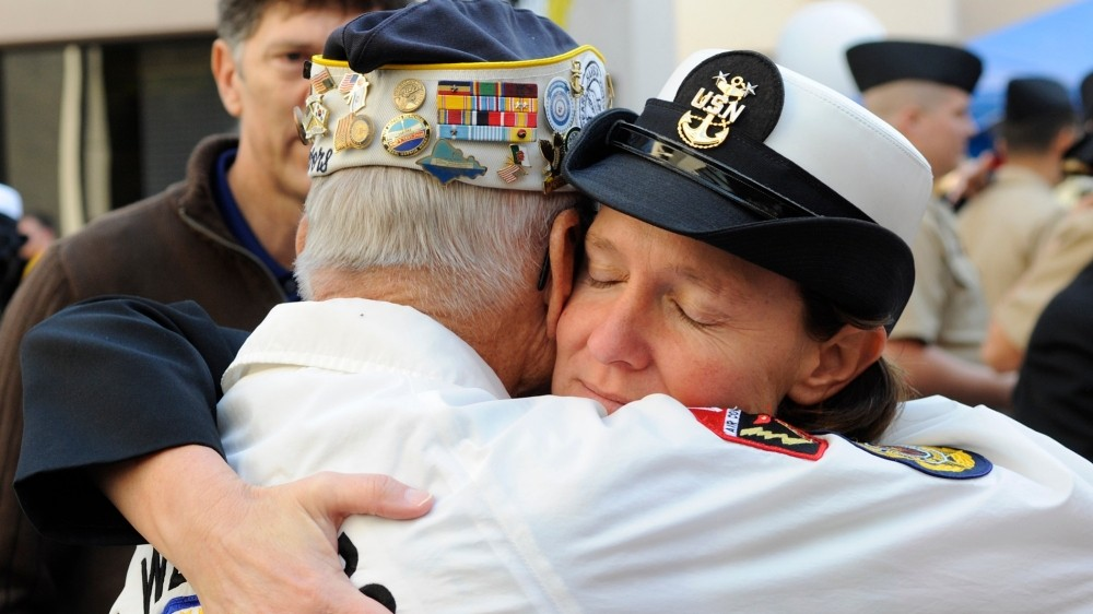 Command Master Chief Kathleen A. Hansen, assigned to Naval Medical Center San Diego, hugs retired Chief Electricians Mate Stuart Hedley during the commemoration of the 68th anniversary of the attack on Pearl Harbor