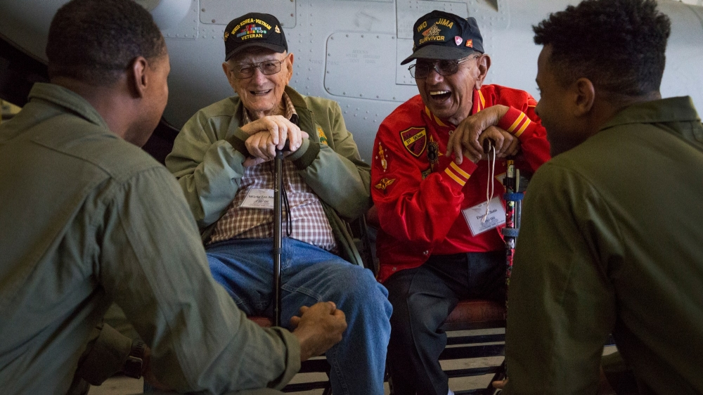 Len Maffioli and Damaso Sutis, two retired Marines and Iwo Jima veterans, share stories and laughs with active-duty Marines