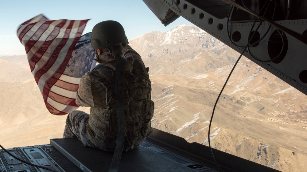Marine Corps Capt. Kimberly Sonntag holds the American flag out the back of a CH-47 Chinook Helicopter