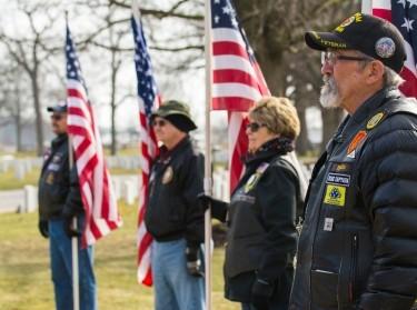 National Veterans Awareness Ride members hold U.S. flags to show support during the National Vietnam War Veterans Day observance