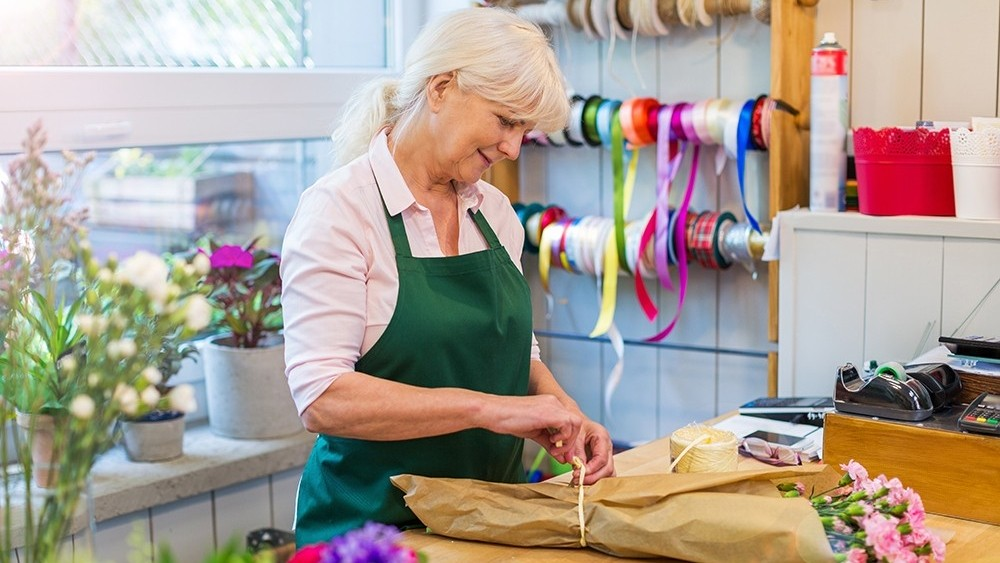 Older woman bundling flowers in a florist shop