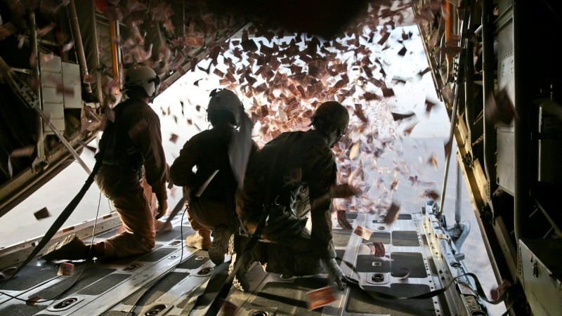 U.S. Marine Corps troops throw leaflets from a KC-130 Super Hercules over southern Afghanistan, Aug. 28, 2013.