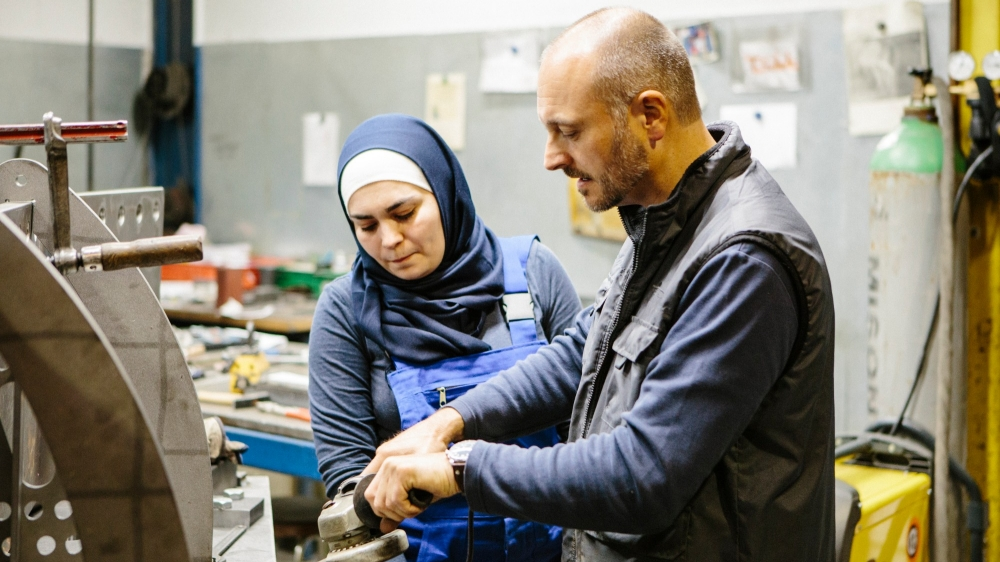 A technician explains how to use a grinder to a female trainee.