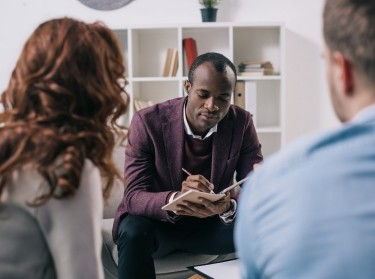 African American psychiatrist writing in textbook with two people in the foreground, photo by Monkey Business Images/Adobe Stock