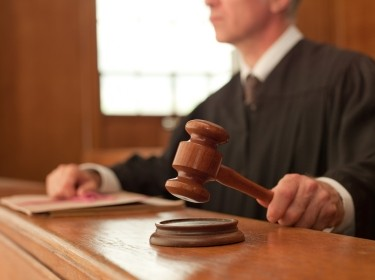 A judge holding a gavel in a courtroom