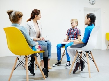 Three elementary school children and a teacher sitting in a circle