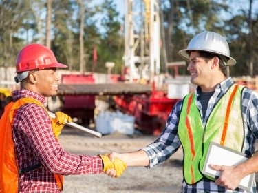 Workers greeting each other at a drilling site