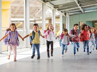Elementary students holding hands and running, photo by monkeybusinessimages/Getty Images