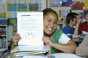 A student holds up her paper.