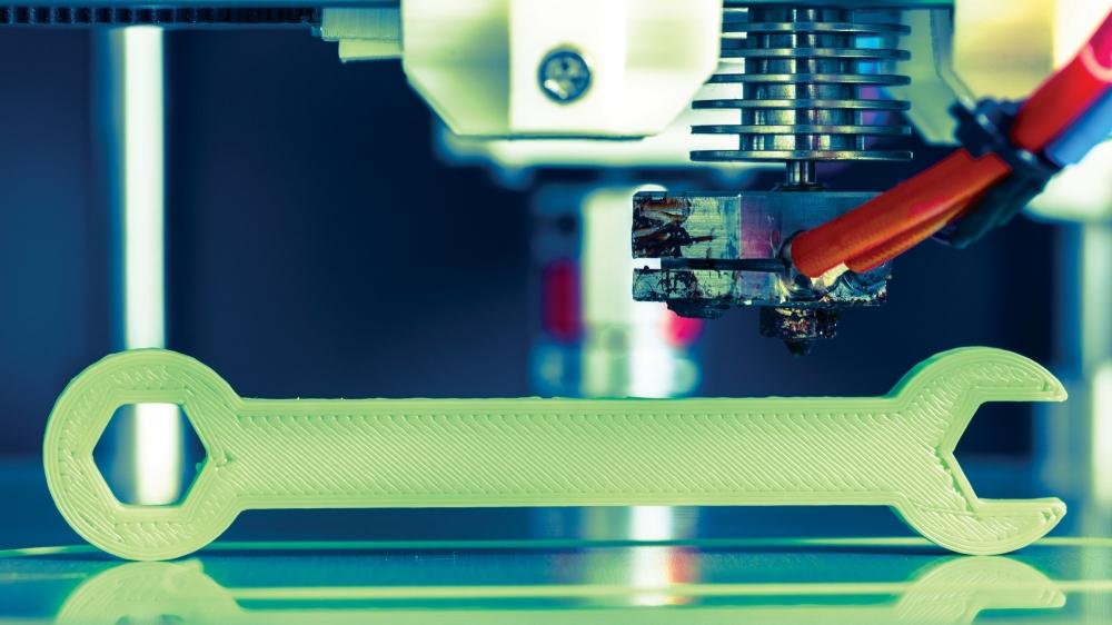 A 3D printer creates a wrench