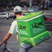 A man on a bike with a large Uber Eats backpack