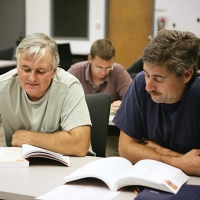 Two men sit at a table during a training class