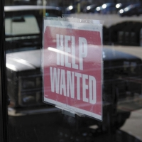 A help wanted sign in a window