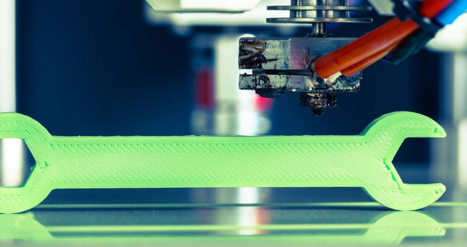 A 3D printer making a wrench with bright green filament