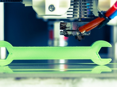 A 3D printer making a wrench with bright green filament, photo by wsf-f/Adobe Stock