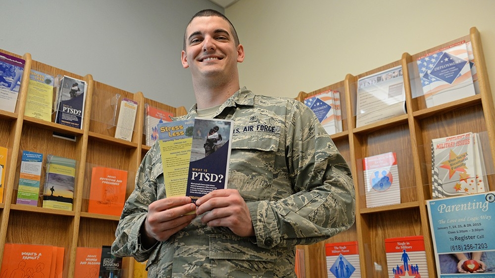 A mental health technician holds PTSD resource brochures