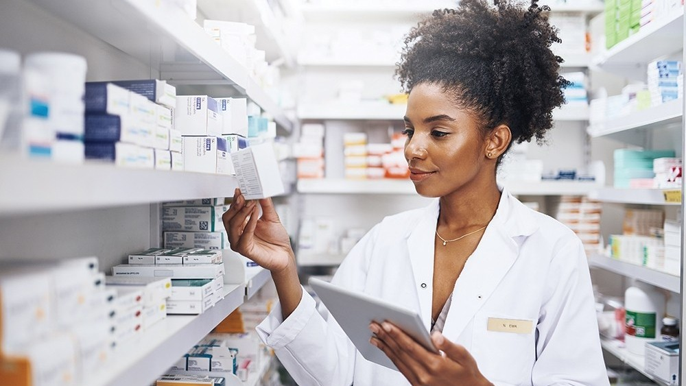 Woman checks stock on a pharmacy shelf