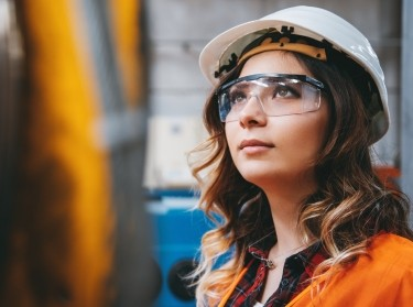 Portrait of young engineer woman working in factory building, photo by serts/Getty Images