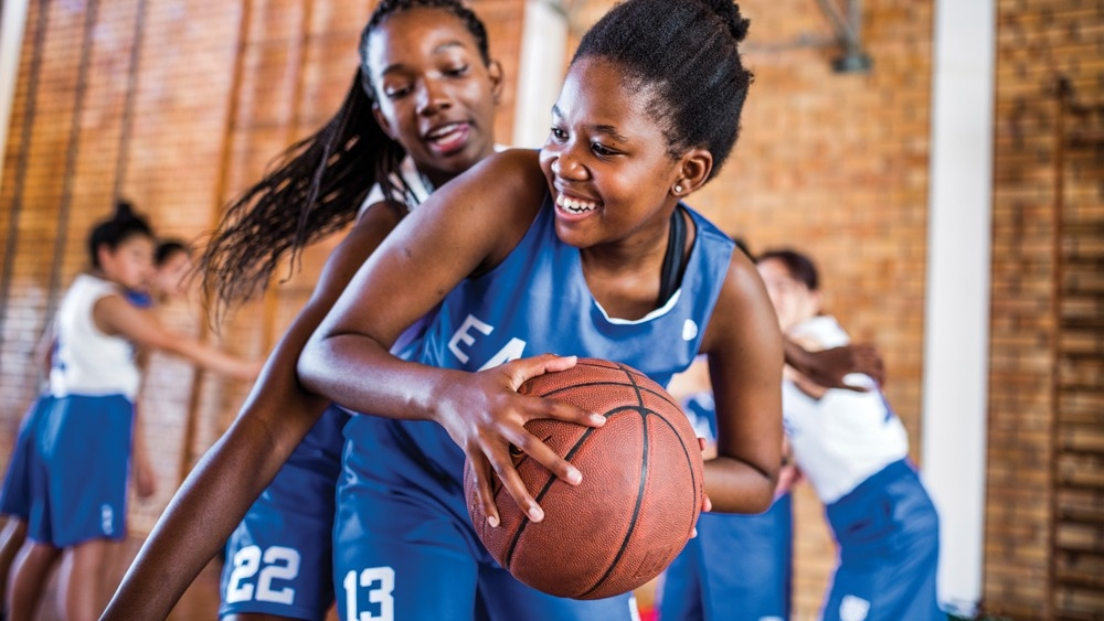 School-age children playing basketball together