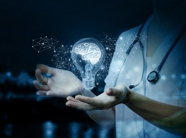 A doctor and a lightbulb depicting innovation in health care, photo by Natali_Mis/Getty Images