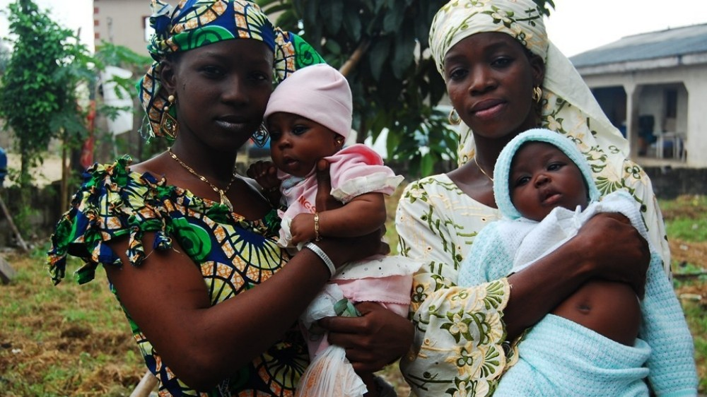 Two Nigerian mothers in Awoyaya, Lagos, hold infants
