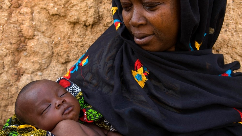 A Nigerian mother holding a sleeping infant