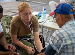 A nurse assigned to the hospital ship USNS Comfort takes a man's blood pressure