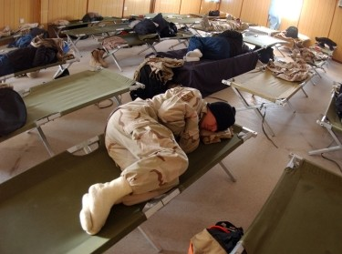 Airmen sleep on cots in a temporary facility