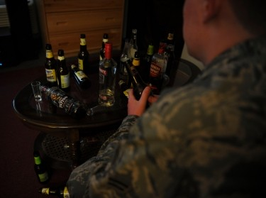 An airman sits before a table filled with empty alcohol containers