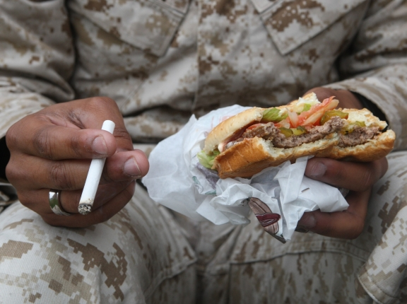An individual in the fatigues worn by U.S. Marines holding a cigarette and hamburger