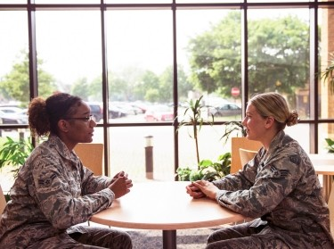 Two U.S. Air Force mental health professionals talk in a hospital reception area