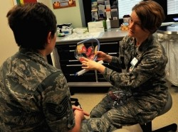 An Air Force OB/GYN physician holds a model of the female reproductive organs
