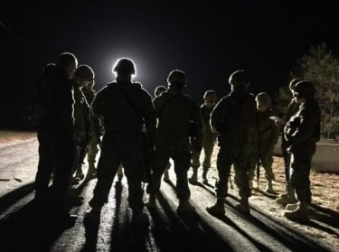 Members of the U.S. Coast Guard port protection force lit from behind at night