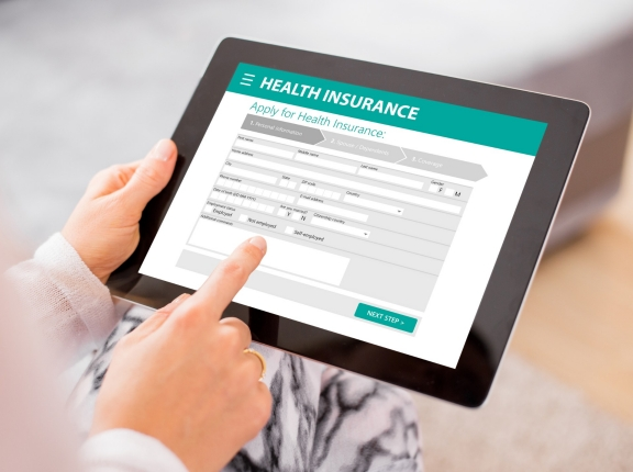 A health insurance application on a tablet, photo by grinvalds/Getty Images