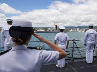 U.S. Navy Sailors salute during an approach to a port in Hawaii
