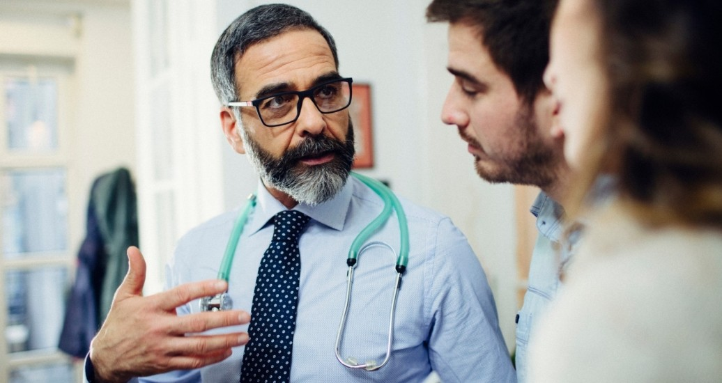 Doctor consulting with a young couple, photo by vgajic/Getty Images
