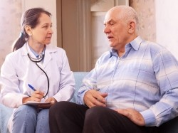 older man speaking with female doctor