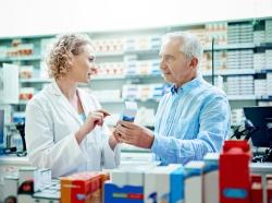 Female pharmacist talking to an elderly man about a prescription