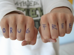 """Letters of the words """"Drug Free"""" written in blue pen on fingers in a fist"""