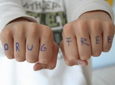 "Letters of the words ""Drug Free"" written in blue pen on fingers in a fist"