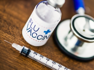 Flu vaccine, syringe, and stethoscope