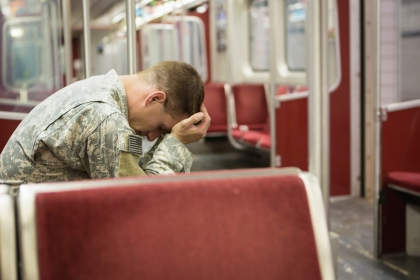 Soldier with head in hands on subway