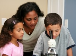 teacher and students at microscope