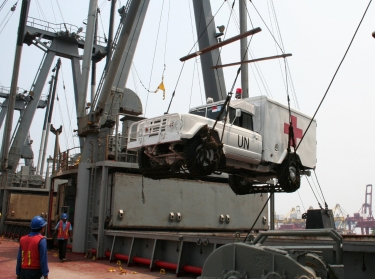 An Indonesian army ambulance, repainted with U.N. peacekeeping colors, is loaded aboard S.S. Wilson.