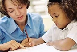 A teacher helps a student.