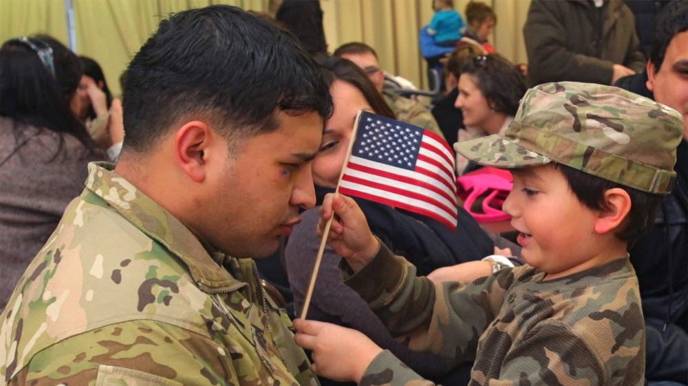 A man and child face each other. The man is wearing camouflage military fatigues. The child is also wearing camouflage, and is holding a small United States flag up to the man.